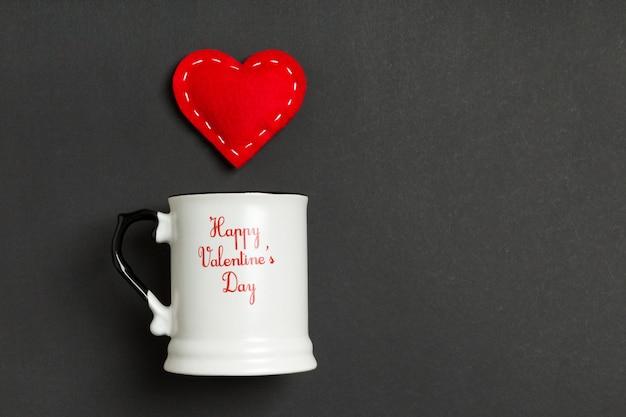 Vista superior composición del corazón rojo cayendo de una taza
