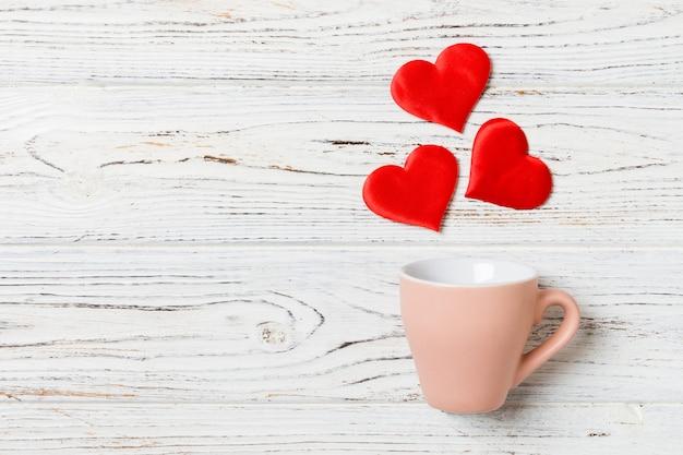 Vista superior de la composición de corazones que salpican de una taza