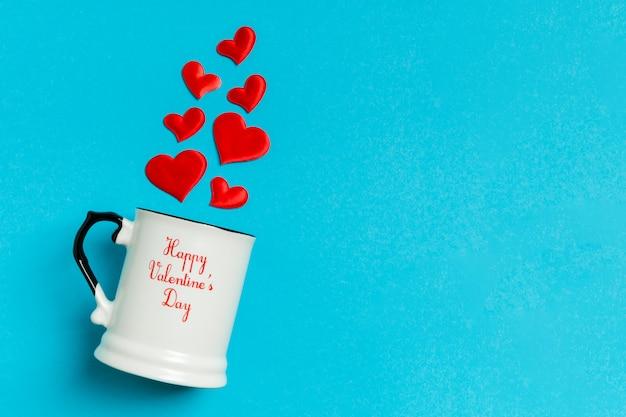 Vista superior composición de corazones rojos cayendo de una taza
