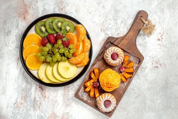 Vista superior composición de diferentes frutas frescas y maduras sobre fondo blanco frutas maduras color suave salud