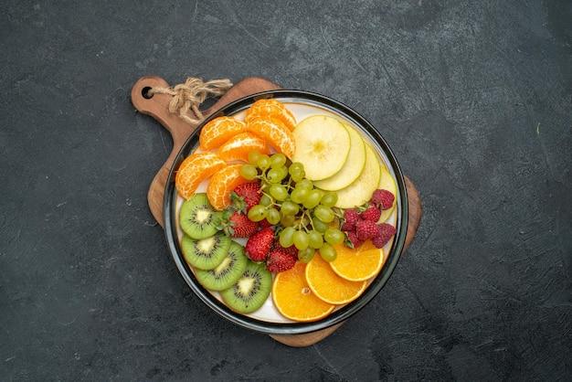 Vista superior de la composición de diferentes frutas frescas en rodajas y maduras sobre fondo gris suaves frutas frescas salud madura