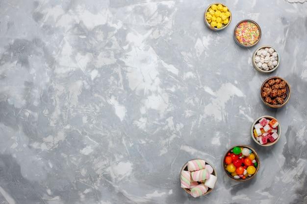 Vista superior de la composición de dulces caramelos de diferentes colores con malvavisco en el escritorio blanco caramelo de azúcar bombón dulce confituras té