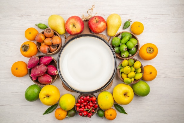 Vista superior de la composición de frutas frescas diferentes frutas en el escritorio blanco dieta color berry cítricos salud árbol maduro sabroso