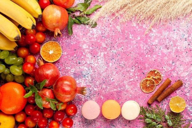 Vista superior de la composición de frutas frescas con macarons franceses en una superficie de color rosa claro