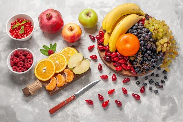 Vista superior de la composición de frutas frescas, plátanos, cornejos y uvas en la superficie de color blanco claro, frutas, bayas, frescura, vitamina
