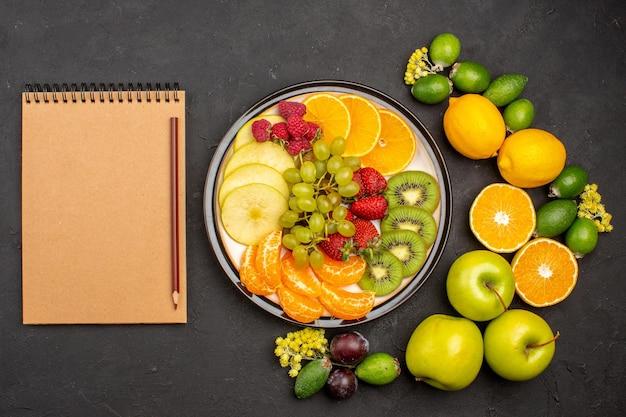 Vista superior de la composición de frutas frescas en rodajas suaves y frutas maduras en la superficie oscura fruta fresca vitamina madura suave