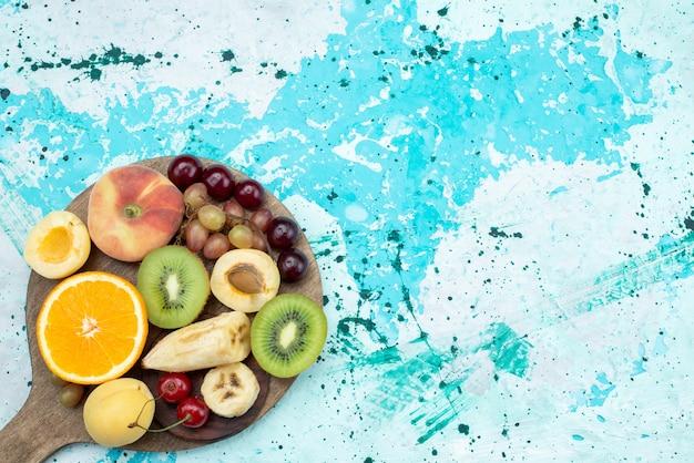 Vista superior de la composición de frutas en rodajas y enteras con galletas en el escritorio de color azul brillante fruta exótica galleta de azúcar