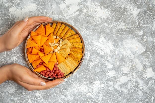 Vista superior de la composición de galletas saladas diferentes bocadillos de galletas saladas con nueces sobre fondo blanco crocante crujiente bocadillos