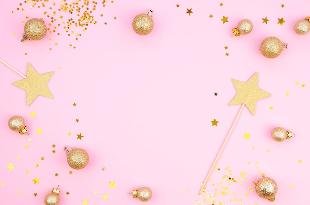 Vista superior de la composición de navidad y año nuevo con decoraciones festivas de invierno dorado sobre un fondo rosa
