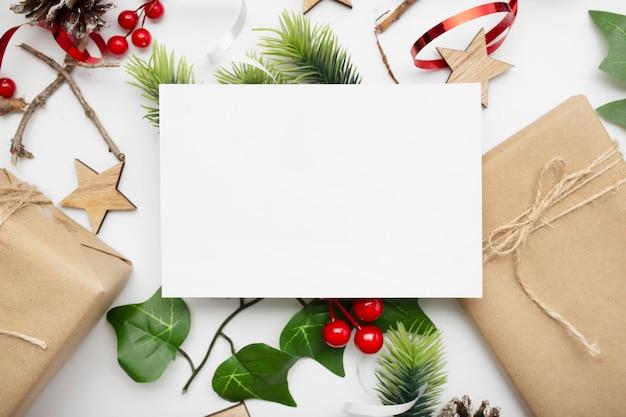 Vista superior de la composición navideña con caja de regalo, cinta, ramas de abeto, conos, anís en mesa blanca
