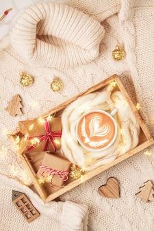 Vista superior de la composición navideña con suéter cálido, regalos, luces de navidad y café.