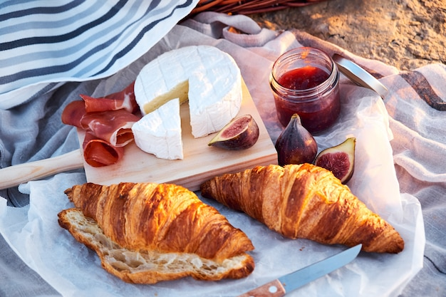 Vista superior de la composición de picnic romántica hermosa con croissants, pan, mermelada, queso, higos y jamón.