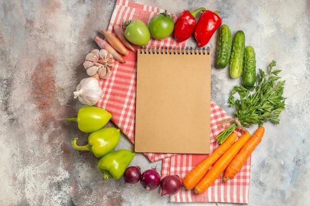 Vista superior composición vegetal pimientos zanahorias ajo y otras verduras sobre fondo blanco.