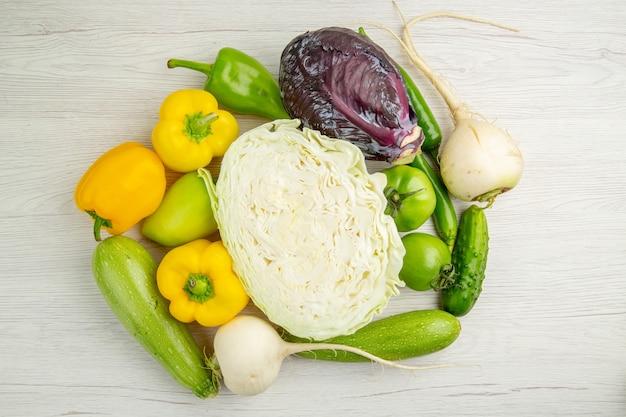 Vista superior composición vegetal repollo pimientos y rábano sobre fondo blanco.