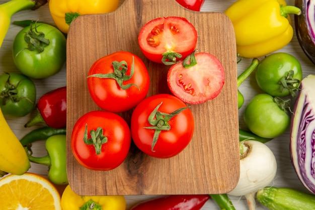 Vista superior composición vegetal tomates repollo pimientos con plátanos sobre fondo blanco.