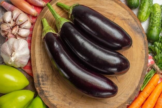 Vista superior de la composición de verduras frescas con berenjenas sobre fondo blanco.