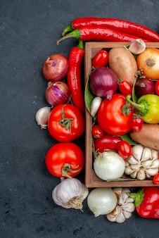 Vista superior de la composición de verduras frescas en color maduro fresco de ensalada de piso gris