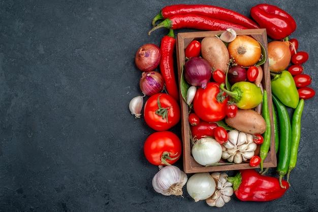 Vista superior de la composición de verduras frescas en ensalada de mesa de color gris oscuro color maduro