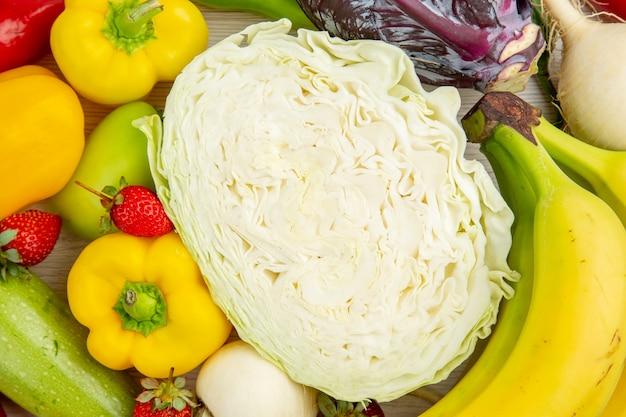 Vista superior de la composición de verduras frescas con frutas en el escritorio blanco