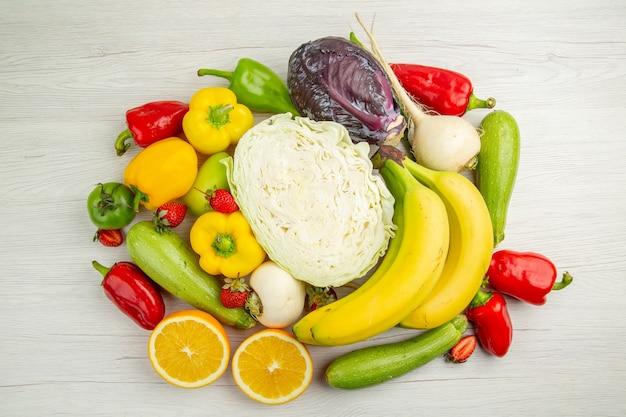 Vista superior de la composición de verduras frescas con frutas sobre fondo blanco.