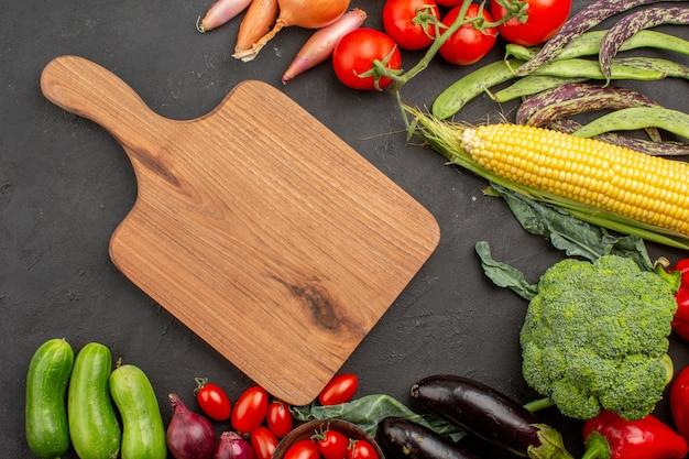 Vista superior de la composición de verduras frescas maduras en el escritorio gris