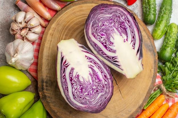 Vista superior de la composición de verduras frescas con repollo rojo en rodajas sobre fondo blanco.
