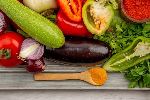 Vista superior de la composición de verduras frescas con verduras y condimentos en la mesa blanca