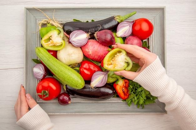 Vista superior de la composición de verduras frescas con verduras dentro del marco en la mesa blanca