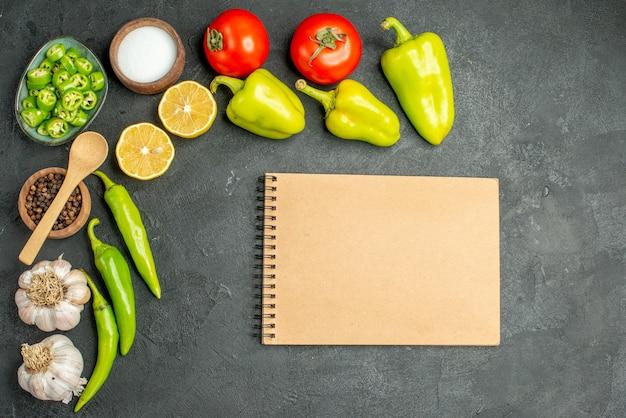 Vista superior de la composición de verduras tomates pimientos y ajos sobre fondo oscuro