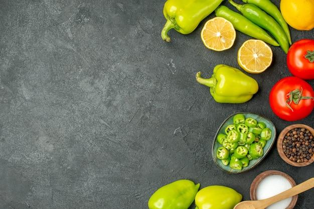 Vista superior de la composición de verduras tomates pimientos y limón sobre fondo oscuro