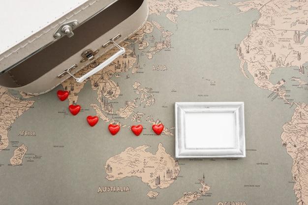 Vista superior de composición de viaje con maleta y marco