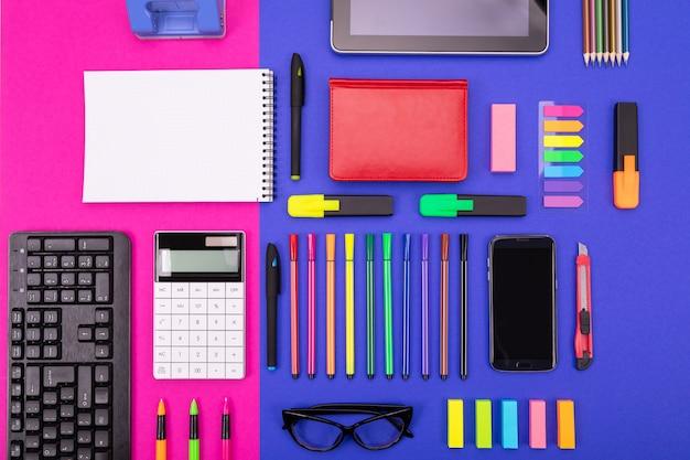 Vista superior del compuesto de escritorio de negocios con teléfono inteligente, calculadora, pegatinas y bolígrafos de color rosa y azul