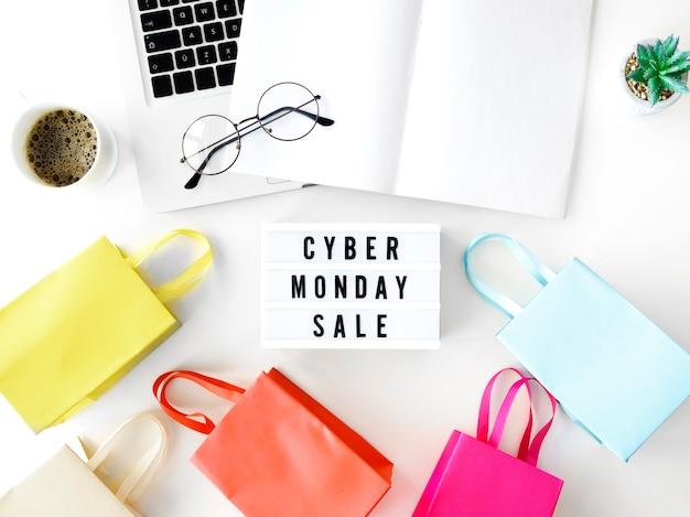 Vista superior de la computadora portátil cyber monday con bolsas de compras y caja de luz