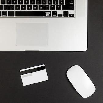 Vista superior de la computadora portátil con mouse y tarjeta de crédito