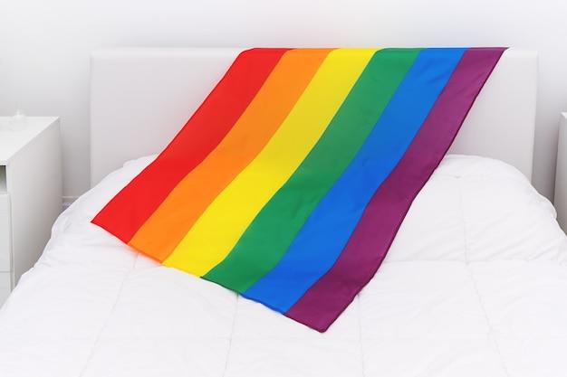 Vista superior de la comunidad lgbt de la bandera del arco iris en la cama blanca