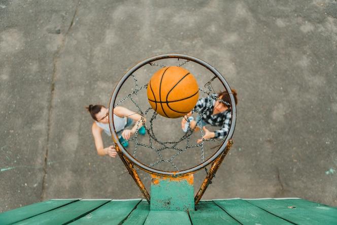 Vista superior con aro de chicas jugando al baloncesto