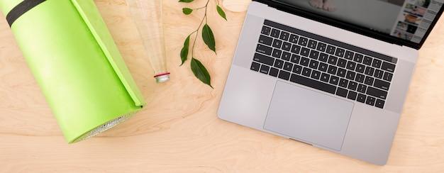 Vista superior del concepto de clase de yoga o deportes de entrenamiento en casa en línea computadora portátil con tapete de yoga en el piso de madera