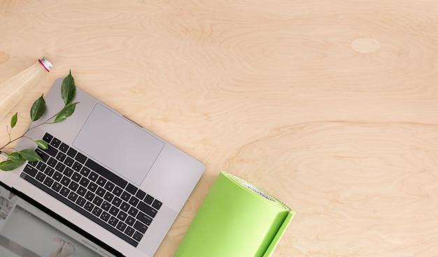 Vista superior del concepto de clase de yoga o deportes de entrenamiento en casa en línea computadora portátil con tapete de yoga en la vista superior del piso de madera