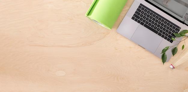Vista superior del concepto de curso de deportes o entrenamiento en línea. laptop con colchoneta de yoga en la vista superior del piso de madera