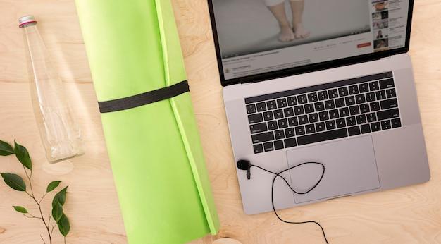 Vista superior del concepto de deporte o curso de entrenamiento en línea computadora portátil con colchoneta de yoga y botella de vidrio en el piso de madera