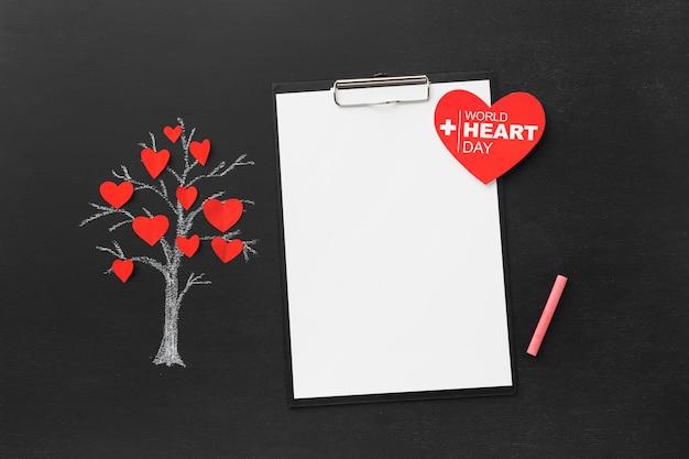 Vista superior del concepto del día mundial del corazón con bloc de notas