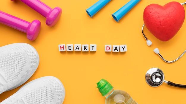 Vista superior del concepto del día mundial del corazón con equipamiento deportivo