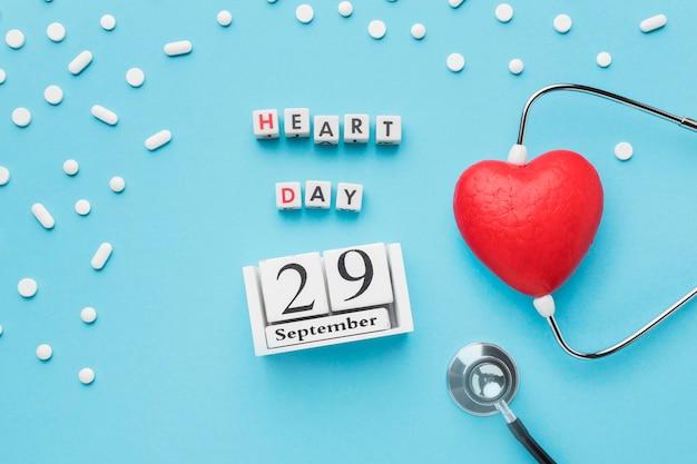 Vista superior del concepto del día mundial del corazón con pastillas