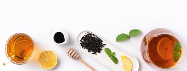 Vista superior del concepto de diseño de té negro de miel con limón amarillo y hojas de menta sobre fondo blanco de mesa.