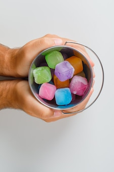 Vista superior del concepto de merienda. manos sosteniendo el cubo de caramelos.