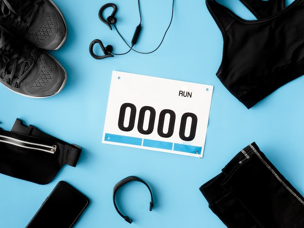 Vista superior del concepto running event con zapatillas, número de babero y accesorios para correr sobre fondo azul.