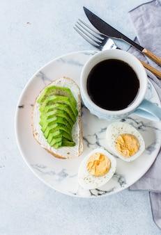 Vista superior del concepto sano del desayuno del vegano. tostadas con aguacate y huevos duros.