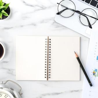 Vista superior del concepto de trabajo de escritorio de mesa de oficina con cuaderno en blanco, informe, reloj despertador sobre fondo blanco de mármol, concepto de gestión de tiempos y planificación de horarios.