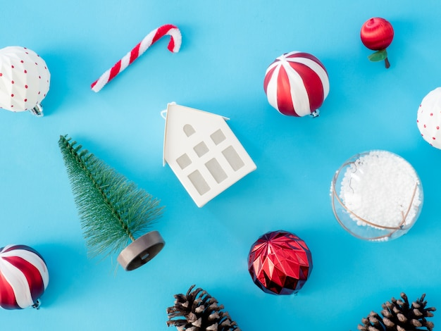 Vista superior del concepto de vacaciones de navidad y año nuevo con piñas, caja de regalo, bola de navidad y decoraciones de navidad en el fondo de la tabla azul.