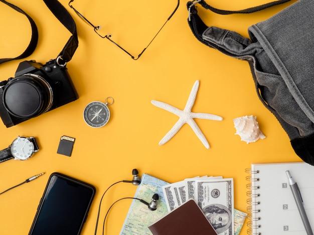 Vista superior del concepto de viaje con cámara, mapa, pasaporte y accesorios de viaje sobre fondo amarillo con espacio de copia, elementos turísticos esenciales, efecto de tono vintage